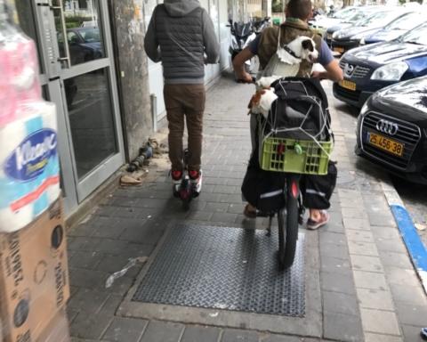 Une vision courante à Tel-Aviv: sur son vélo électrique ce conducteur lourdement chargé transporte en outre trois chiens et roule sur le trottoir (photo: KHC).