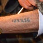 Un survivant de la Shoah montrant le numéro tatoué sur son bras par les nazis (photo : Frankie Fouganthin - Own work, CC BY-SA 3.0, https://commons.wikimedia.org/w/index.php?curid=24277501).