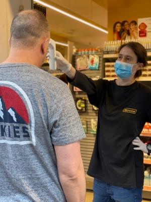 L'employée d'une pharmacie à Tel-Aviv vérifiant que le client n'a pas de fièvre (photo : KHC).