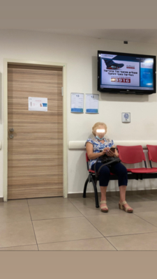 Une dame d'un certain âge attendant son tour chez le médecin. Au lieu de porter son masque sur le visage, elle le porte sur le menton. Le manque de discipline de nombreux Israéliens concernant le port du masque est flagrant (photo: KHC).